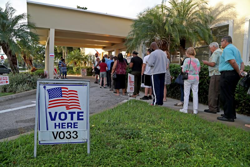 Voters line up at a community center in Hollywood, Fla.