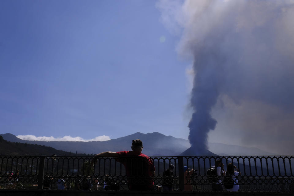 A man looks towards a volcano as it continues to erupt in El Paso on the canary island of La Palma, Spain, Saturday Oct. 9, 2021. A new lava flow has belched out from the La Palma volcano and it threatens to spread more destruction on the Atlantic Ocean island where molten rock streams have already engulfed over 1,000 buildings. The partial collapse of the volcanic cone overnight sent a new lava stream Saturday heading toward the western shore of the island. (AP Photo/Daniel Roca)