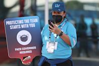 A worker holds a 'face coverings required' sign before Super Bowl LV between the Tampa Bay Buccaneers and the Kansas City Chiefs at Raymond James Stadium on February 07, 2021 in Tampa, Florida. (Photo by Patrick Smith/Getty Images)