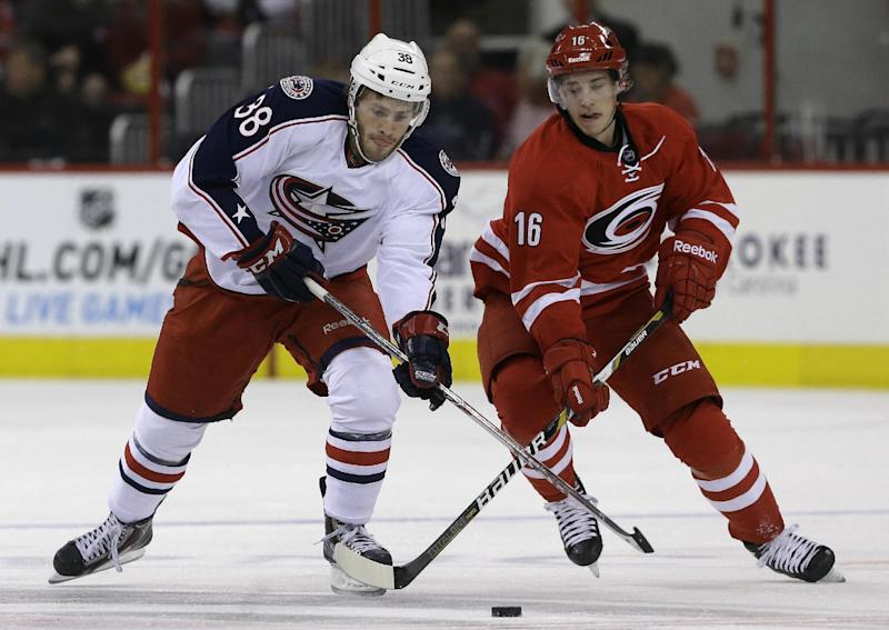Carolina Hurricanes' Elias Lindholm (16), of Sweden, and Columbus Blue Jackets' Boone Jenner (38) chase the puck during the first period of an NHL preseason hockey game in Raleigh, N.C., Wednesday, Sept. 18, 2013. (AP Photo/Gerry Broome)