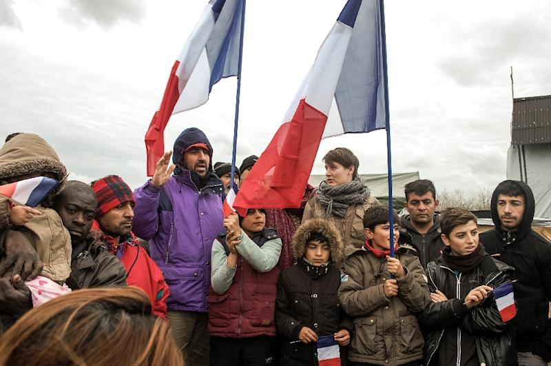 """Migrants and refugees in the Calais migrant camp known as """"the Jungle"""" observe a minute of silence on November 20, 2015, a week after jihadist attacks in Paris left 130 people dead and more than 350 injured"""