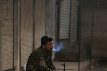 A Syria Democratic Forces (SDF) fighter smokes a cigarette in the city of Manbij, in Aleppo Governorate, Syria, August 10, 2016. REUTERS/Rodi Said