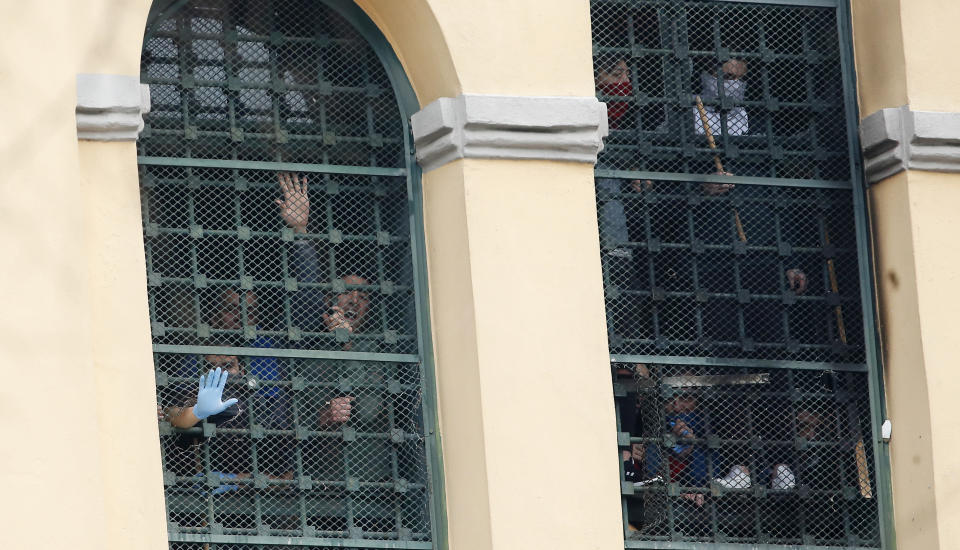 Inmates stand behind bars at the San Vittore prison as protests broke out following restrictions that were imposed on family visits to prevent coronavirus transmissions, in Milan, Italy, Monday, March 9, 2020. Italian penitentiary police say six inmates protesting virus containment measures at the northern Italian prison of Modena have died after they broke into the infirmary and overdosed on methadone. The protest Sunday in Modena was among the first of more than two-dozen riots at Italy's overcrowded lock-ups that grew Monday. (AP Photo/Antonio Calanni)