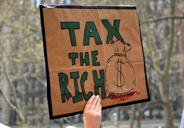 Protester holding up sign that says 'tax the rich'