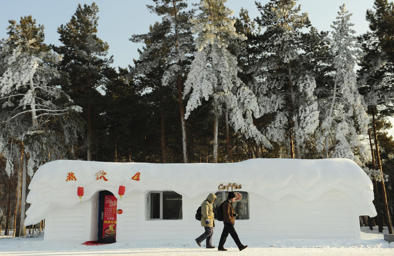 Tourists walk past a coffee shop covered by shaped snow ahead of the 13th Harbin Ice and Snow World in Harbin, Heilongjiang province December 26, 2011. The Harbin International Ice and Snow Festival will be officially launched on January 5, 2012. REUTERS/Sheng Li (CHINA - Tags: ENVIRONMENT SOCIETY)