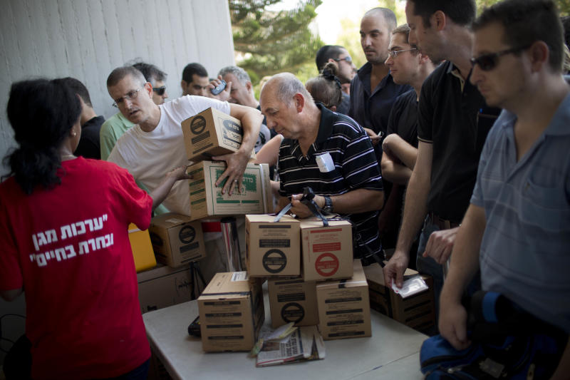 Israelis line up at a gas mask distribution center in Tel Aviv, Israel, Wednesday, Aug. 28, 2013. Large crowds of Israelis have lined up at gas-mask distribution centers across the country in anticipation of a possible Syrian attack on Israel. (AP Photo/Oded Balilty)