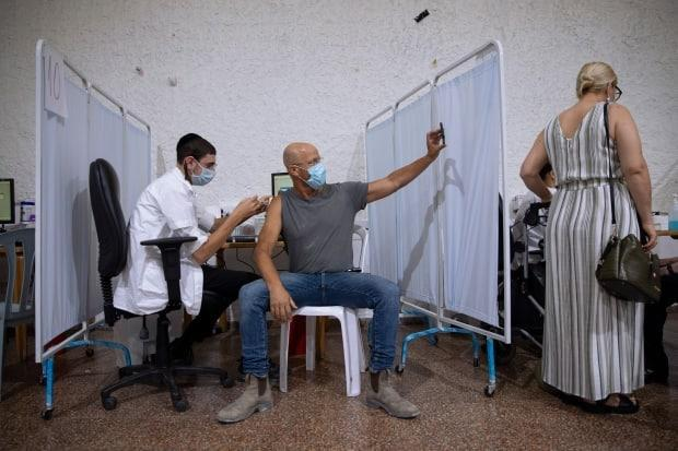 A man takes a selfie while receiving the third Pfizer-BioNTech COVID-19 vaccine from medical staff at a coronavirus vaccination center in Ramat Gan, Israel on Aug. 30.  (Oded Balilty/The Associated Press - image credit)
