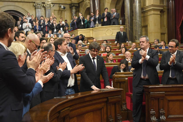 Catalan Regional Government President Carles Puigdemont, center, acknowledging applause from colleagues. (Photo: Luis Gene/AFP/Getty Images)