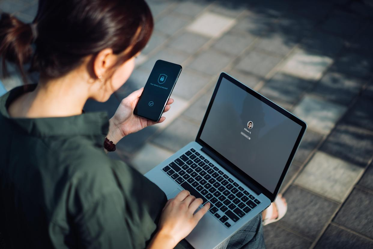 Young Asian businesswoman sitting on the bench in an urban park working outdoors, logging in to her laptop and holding smartphone on hand with a security key lock icon on the screen. Privacy protection, internet and mobile security concept