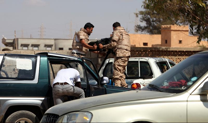 Soldiers from the Libyan National Army get ready to enter Rafallah al-sahati Islamic Militia Brigades compound, the compound buildings can be seen behind the wall, in Benghazi, Libya, Saturday, Sept. 22, 2012. On Friday evening hundreds of protesters angry over last week's killing of the U.S. ambassador to Libya stormed the compound of the Islamic extremist Ansar al-Shariah Brigade militia suspected in the attack, evicting militiamen and setting fire to their building. After taking over the Ansar compound, protesters then drove to attack the Benghazi headquarters of Rafallah Sahati where militiamen opened fire on the protesters, who were largely unarmed leaving at least 20 wounded, and several killed according to hospital sources. (AP Photo/Mohammad Hannon)