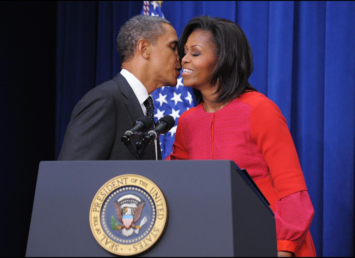 First Lady Michelle Obama kisses US President Barack Obama after introducing him during a signing ceremony for a bill which provides tax credits to companies to put veterans back to work November 21, 2011 in the South Court Auditorium, next to the White House in Washington, DC. AFP PHOTO/Mandel NGAN (Photo credit should read MANDEL NGAN/AFP/Getty Images)