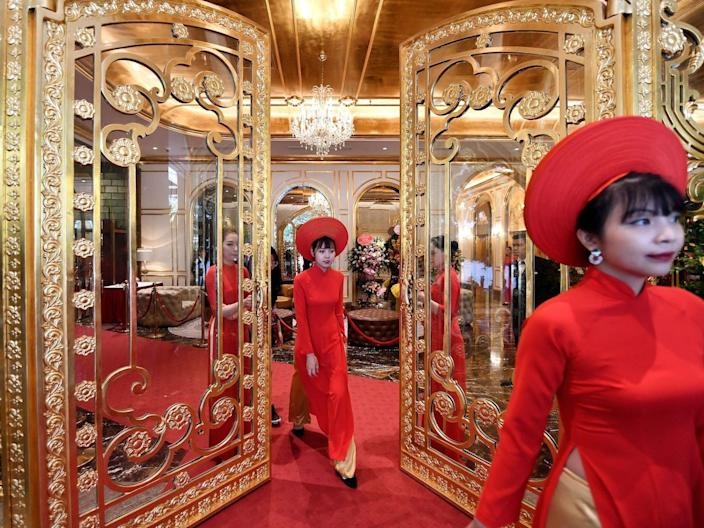 Staff wait to welcome guests in the lobby of the newly-inaugurated Dolce Hanoi Golden Lake hotel in Hanoi, Vietnam, on July 2, 2020.