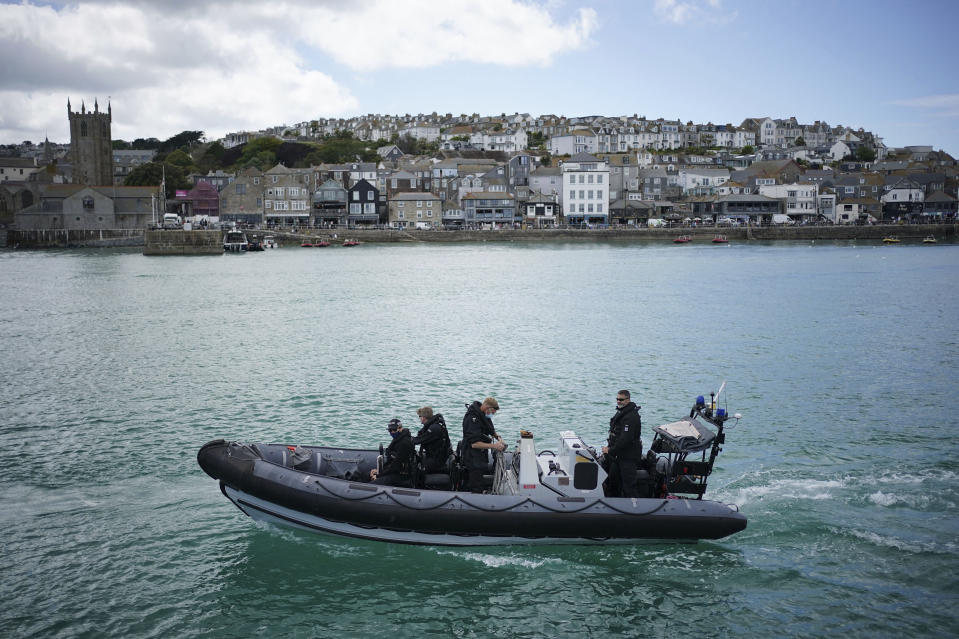 FILE - In this Monday, June 7, 2021 file photo, police officers patrol the harbour in St. Ives, Cornwall, England ahead of the G7 summit that takes place in nearby Carbis Bay. Towering steel fences and masses of police have transformed the Cornish seaside as leaders of the Group of Seven wealthy democracies descent for a summit near St. Ives in Cornwall, a popular holiday destination. A huge frigate dominates the coastline, armed soldiers guard the main sites and some 5,000 extra police officers have been deployed to the area. (Aaron Chown/PA via AP, File)