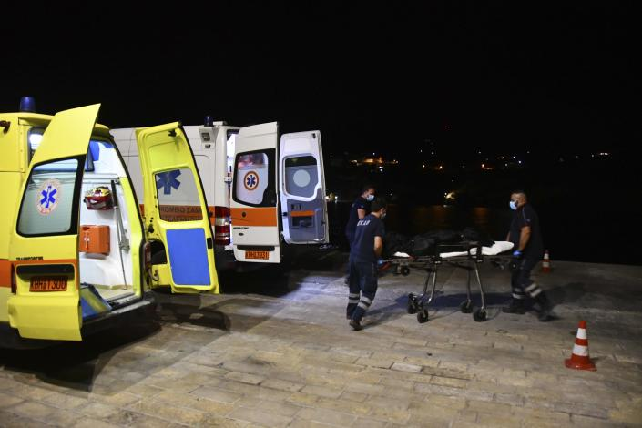 Paramedics wheel a gurney with a body at Pythagorio port, on the eastern Aegean island of Samos, Greece, late Monday, Sept. 13, 2021. Authorities in Greece Tuesday opened an investigation into the crash of a private plane from Israel that killed a prosecution witness in the corruption trial of former Israeli prime minister Benjamin Netanyahu. Haim Geron, a former senior official at Israel's ministry of communications, and his wife Esther were killed in the crash late Monday off the island of Samos. (AP Photo/Michael Svarnias)