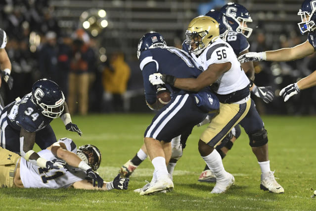 Connecticut quarterback Jack Zergiotis (11) is sacked by Navy linebacker Nizaire Cromartie (56) during the first half of an NCAA college football game Friday, Nov. 1, 2019, in East Hartford, Conn. (AP Photo/Stephen Dunn)
