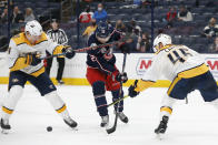 Columbus Blue Jackets' Emil Bemstrom, center, tries to shoot the puck between Nashville Predators' Mikael Granlund, left, and Alexandre Carrier during the second period of an NHL hockey game Wednesday, May 5, 2021, in Columbus, Ohio. (AP Photo/Jay LaPrete)