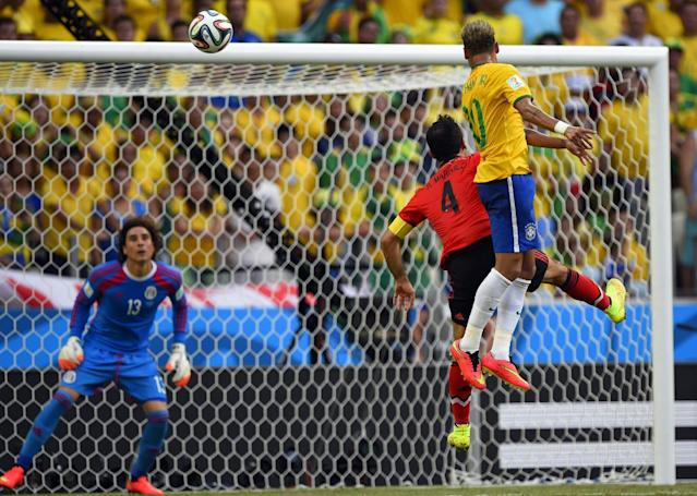 Brazil's forward Neymar (R) and Mexico's defender Rafael Marquez (C) jump for the ball in front of Mexico's goalkeeper Guillermo Ochoa during a World Cup match in Fortaleza on June 17, 2014 (AFP Photo/Odd Andersen)