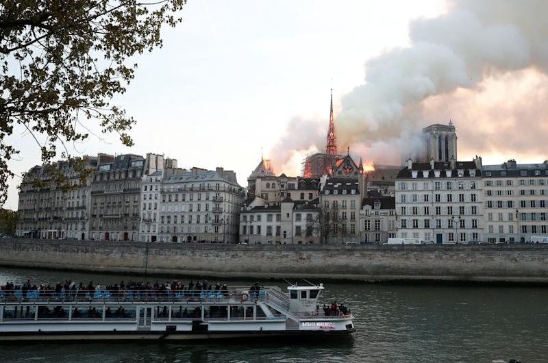 People watch from a tour boat on the River Seine as smoke billows and fire engulfs the spire of Notre Dame Cathedral in Paris, France April 15, 2019. REUTERS/Benoit Tessier