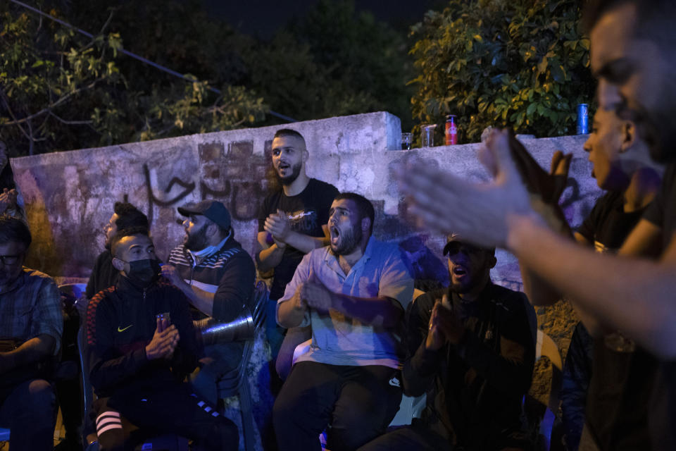Palestinians sing during an ongoing protest against the forcible eviction of Palestinians from their homes in the Sheikh Jarrah neighborhood of east Jerusalem, Friday, May 7, 2021. Dozens of Palestinian families in east Jerusalem are at risk of losing their homes to Jewish settler groups following a decades-long legal battle. The threatened evictions have sparked weeks of protests and clashes in recent days, adding to the tensions in Jerusalem. (AP Photo/Maya Alleruzzo)