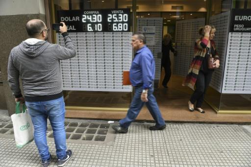 Currency exchange values are displayed on the buy-sell board of an exchange business in Argentina, where the peso has plummeted to a new low