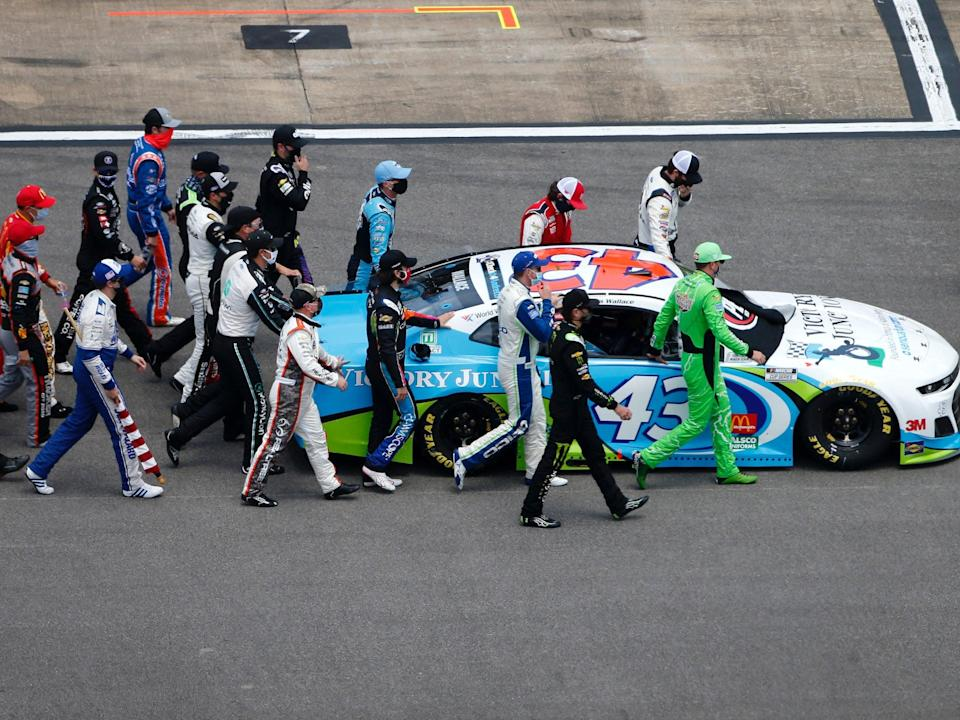 Drivers walk Bubba Wallace's No. 43 car to the front of the grid prior to the GEICO 500.