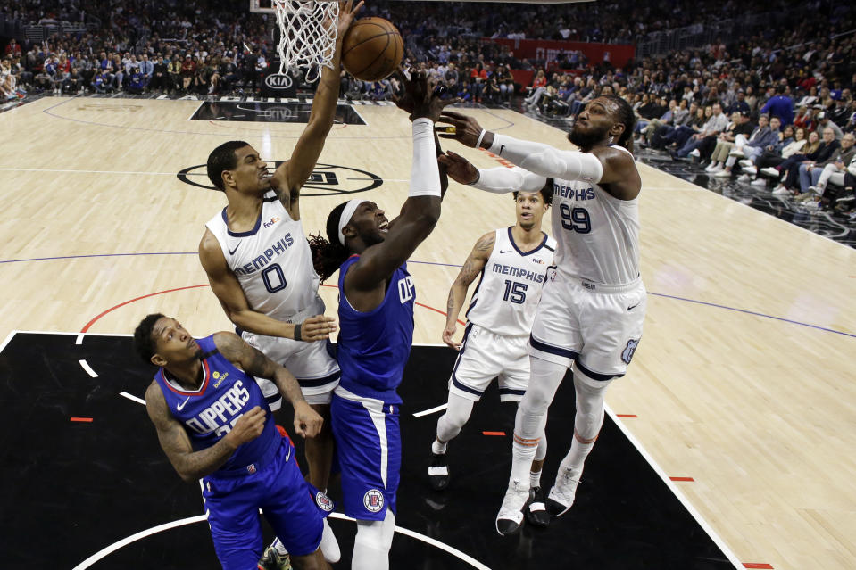 Los Angeles Clippers' Montrezl Harrell, center, tries to grab a rebound between Memphis Grizzlies' De'Anthony Melton (0) and Jae Crowder (99) during the second half of an NBA basketball game Saturday, Jan. 4, 2020, in Los Angeles. (AP Photo/Marcio Jose Sanchez)