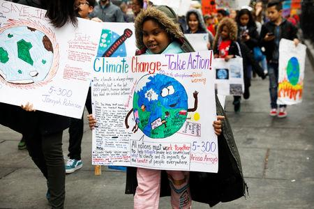 Students hold banners and placards during a demonstration against climate change in New York, U.S., March 15, 2019. REUTERS/Shannon Stapleton