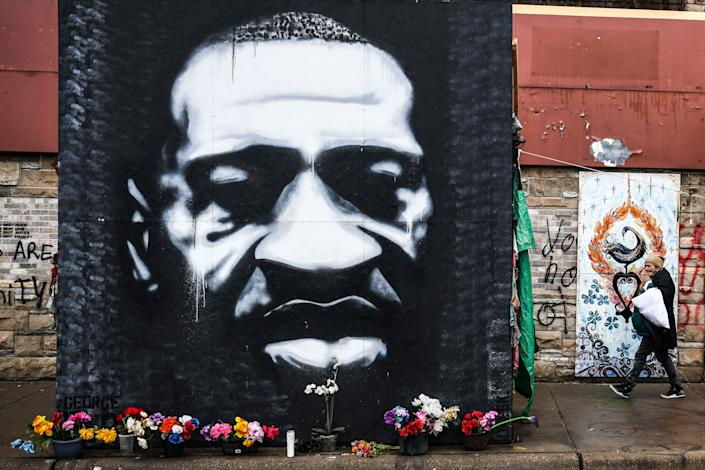A woman walks near the makeshift memorial of George Floyd before the third day of jury selection begins in the trial of former Minneapolis Police officer Derek Chauvin who is accused of killing Floyd, in Minneapolis, Minnesota on March 10, 2021. (Photo by CHANDAN KHANNA / AFP) (Photo by CHANDAN KHANNA/AFP via Getty Images)