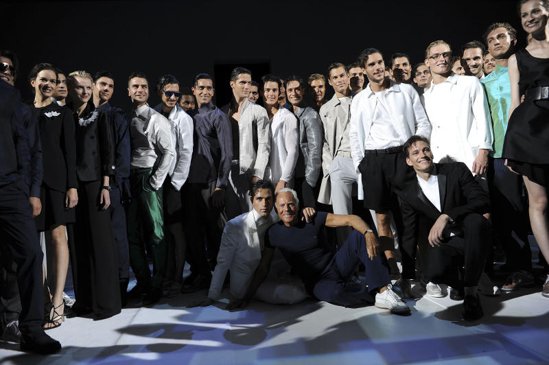 Fashion designer Giorgio Armani, sitting on the ground at center, poses with his models at the end of the men's Spring-Summer 2014 collection part of the Milan Fashion Week, unveiled in Milan, Italy, Monday, June 24, 2013. (AP Photo/Giuseppe Aresu)