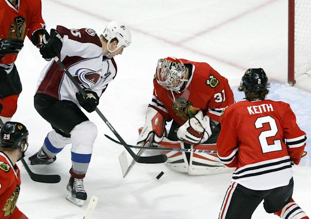 Chicago Blackhawks goalie Antti Raanta (31) makes a save on a shot by Colorado Avalanche left wing Cody McLeod, as defenseman Duncan Keith (2) watches during the first period of an NHL hockey game Friday, Dec. 27, 2013, in Chicago. (AP Photo/Charles Rex Arbogast)