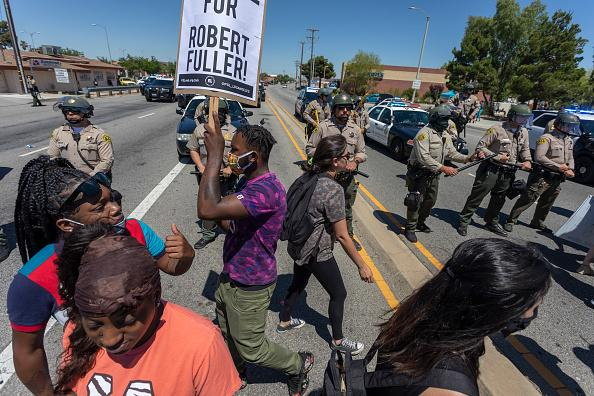 Sheriffs block marchers from continuing down East Palmdale Boulevard after leaving a demonstration at the tree that authorities say Robert Fuller, a 24-year-old black man, was found hanging dead from near Palmdale City Hall.