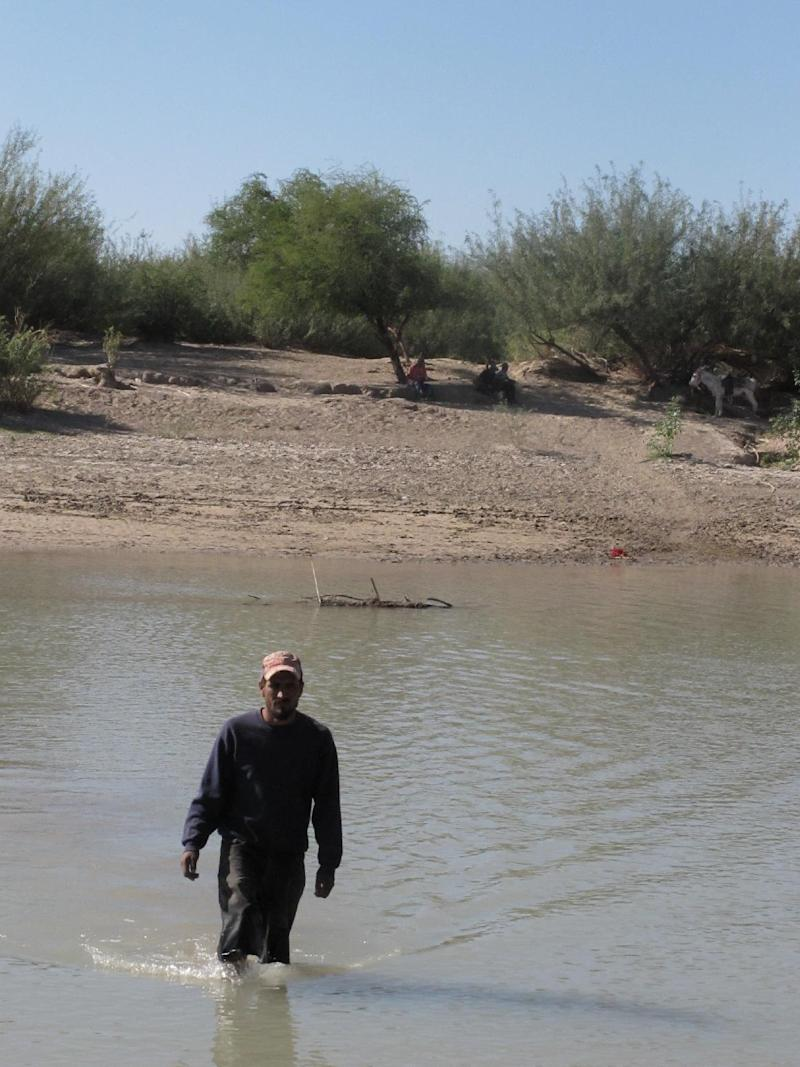 In this Oct. 31, 2011 photo, Guillermo Gonzalez Diaz, resident of Boquillas del Carmen, Mexico, wades into the Rio Grande across from Big Bend National Park, Texas. In this rugged, remote West Texas terrain where wading across the shallow Rio Grande undetected is all too easy, federal authorities are touting a proposal to open an unmanned port of entry as a security upgrade. If approved, the crossing would be the nation's first such port of entry with Mexico.  (AP Photo/Christopher Sherman)