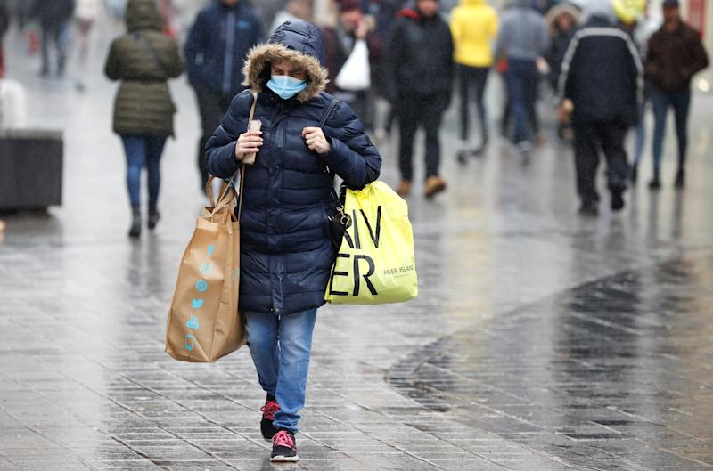 A woman wearing a face mask carries shopping bags amid the outbreak of the coronavirus disease (COVID-19) in Liverpool, Britain, October 12, 2020. REUTERS/Phil Noble