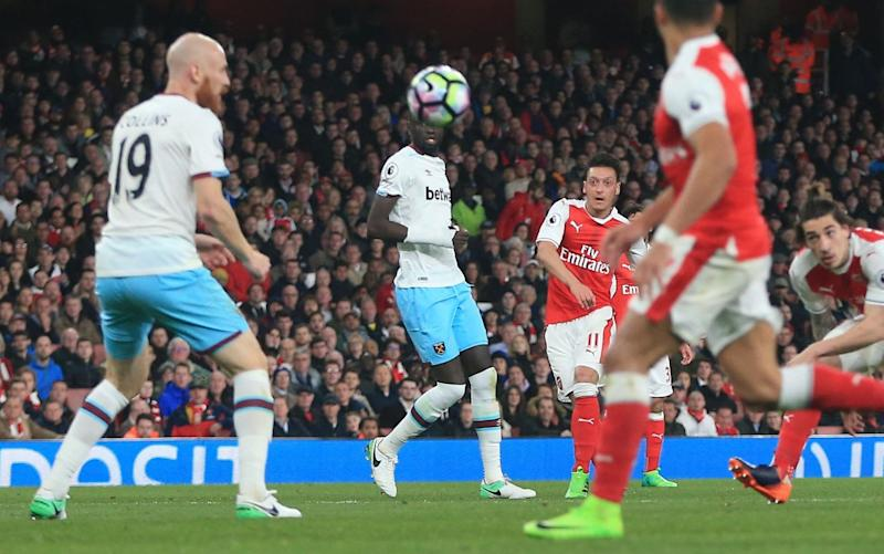 Mesut Ozil puts Arsenal in front from the edge of the box - Rex Features