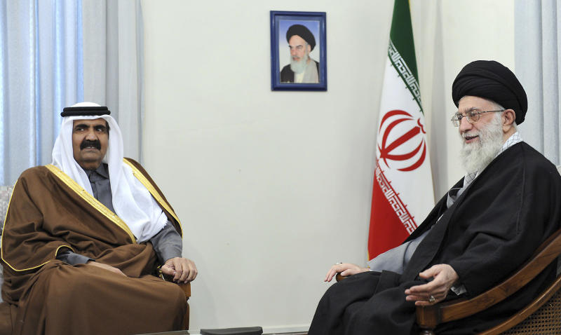 In this photo released by the official website of the Iranian supreme leader's office, Iranian supreme leader Ayatollah Ali Khamenei, right, talks with Qatari Emir Sheik Hamad Bin Khalifa Al Thani, during their meeting in Tehran, Iran, Monday, Dec. 20, 2010. A picture of the late Iranian revolutionary founder Ayatollah Khomeini hangs on the wall. (AP Photo/Office of the Supreme Leader) EDITORIAL USE ONLY, NO SALES
