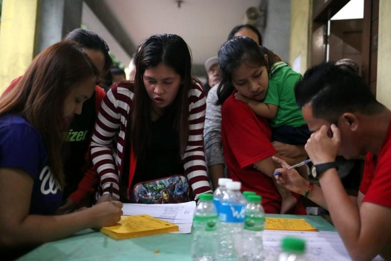 Families register their names at the Delpan Evacuation Center after Typhoon Kammuri hit Metro Manila,