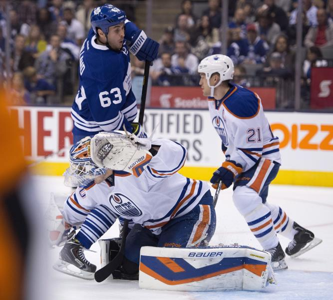 Toronto Maple Leafs Dave Bolland (63) picks up a goaltender interference call as he runs into Edmonton Oilers goaltender Devan Dubnyk during the second period of an NHL hockey game, Saturday, Oct. 12, 2013 in Toronto. (AP Photo/The Canadian Press, Frank Gunn)