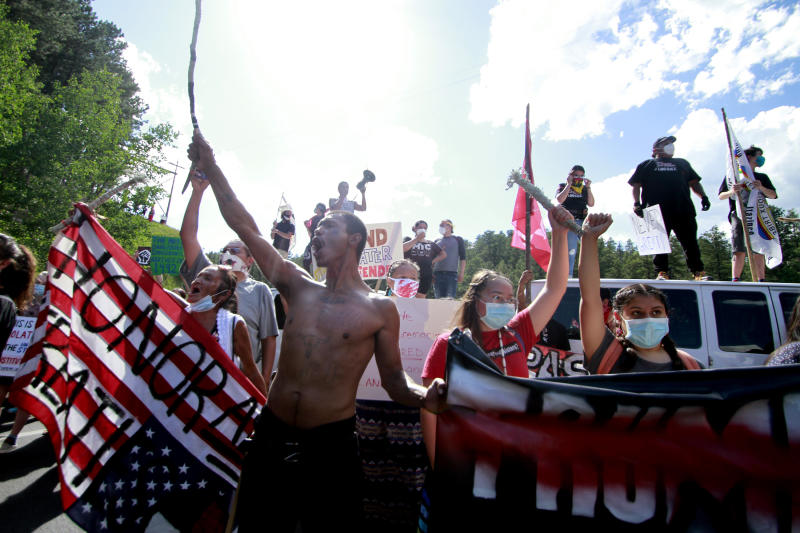 Native American protesters form a roadblock on the road leading to Mount Rushmore ahead of President Donald Trump's visit to the memorial on Friday, July 3, 2020, in Keystone, S.D. (AP Photo/Stephen Groves)
