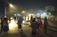 In this image taken from video, people stand outside their homes and gather together on a road in Insein township in Yangon, Myanmar, Monday, March 8, 2021. Demonstrators in Myanmar's biggest city came out Monday night for their first mass protests in defiance of an 8 p.m. curfew, seeking to show support for an estimated 200 students trapped by security forces in a small area of one neighborhood. (AP Photo)