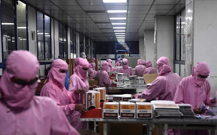 Workers pack syringes at the Hindustan Syringes factory in Faridabad. - Sajjad Hussain/ AFP
