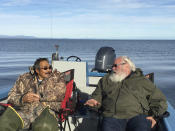 In this Aug. 25, 2016, photo provided by the Maniilaq Association, Cyrus Harris with the Maniilaq Association, left, discusses seal oil with Eric Johnson ,of the University of Wisconsin, near Kotzebue, Alaska. In January 2021, the Alaska Department of Environmental Conservation approved seal oil to be served at a Maniilaq elder care home, believed to be a first for seal oil in the United States. (Maniilaq Association via AP)