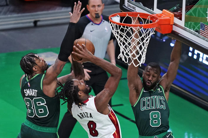 Miami Heat forward Trevor Ariza, center, is blocked by Boston Celtics' Marcus Smart (36) and guard Kemba Walker, right, on a drive to the basket during the first half of an NBA basketball game Tuesday, May 11, 2021, in Boston. (AP Photo/Charles Krupa)