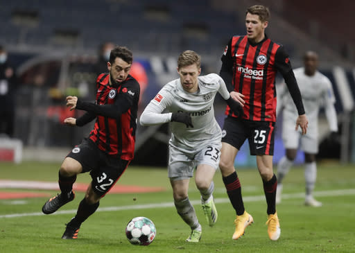 Leverkusen's Mitchell Weiser, center, and Frankfurt's Amin Younes, left, challenge for the ball during a German Bundesliga soccer match between Eintracht Frankfurt and Bayer Leverkusen in Frankfurt, Germany, Wednesday, Dec. 23, 2020. (AP Photo/Michael Probst)