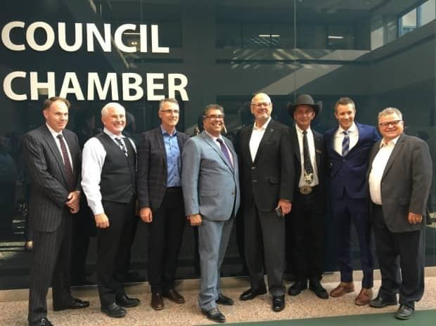 Representatives from the three groups behind the Flames arena deal pose for a photo after it was approved by council. From left: Barry Munro, who handled negotiations for the city; Coun. Ward Sutherland; John Bean of CSEC; Mayor Naheed Nenshi; Ken King of CSEC; Stampede CEO Warren Connell; Coun. Jeff Davison; and Coun. Shane Keating.