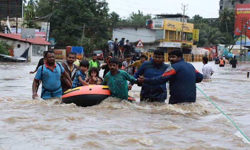 Volunteers and rescue workers evacuate local residents from Ernakulam district
