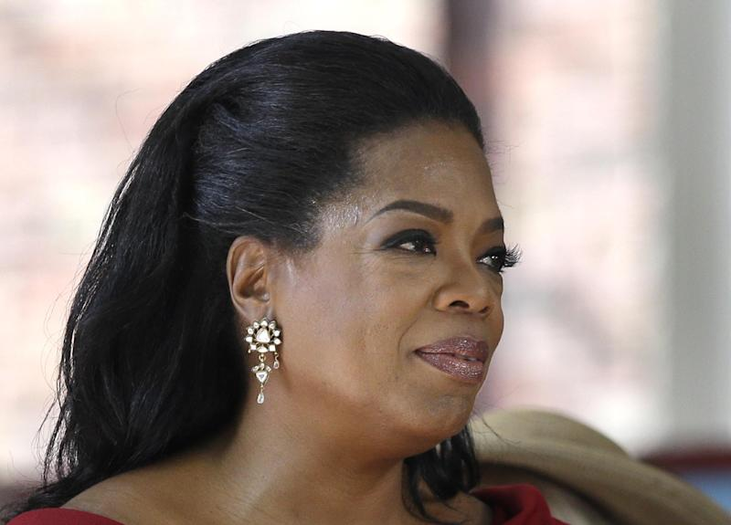 FILE - In this May 30, 2013 file photo Oprah Winfrey reacts after delivering the commencement address at Harvard University in Cambridge, Mass. Winfrey is giving $12 million to a museum being built on the National Mall that will document African-American life. The National Museum of African American History and Culture said the museum's 350-seat theater will be named after Winfrey. When it's finished in 2015, the museum will house artifacts including Harriet Tubman's shawl, Emmett Till's casket and a Jim Crow-era segregated railroad car.(AP Photo/Elise Amendola, File)
