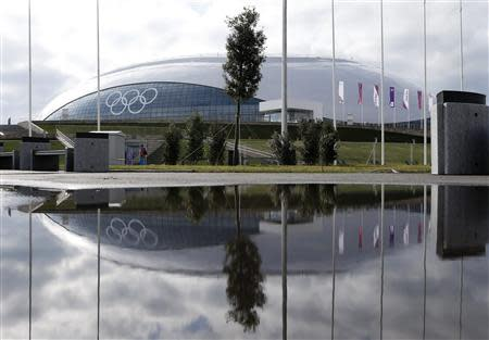 The Bolshoy Ice Dome is reflected in a puddle of water on the Olympic Park as preparations continue for the Sochi 2014 Winter Olympics