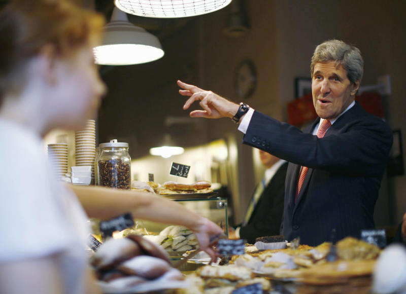 "U.S. Secretary of State John Kerry buys pastries from Cafe Baguette during a walking tour of central Warsaw, Tuesday Nov. 5, 2013. Kerry is vowing that a review into NSA surveillance activities will ultimately result in the ""right"" balance between security and privacy and says outrage over alleged espionage and eavesdropping should not disrupt key trade talks between Europe and the United States. (AP Photo/Jason Reed, Pool)"