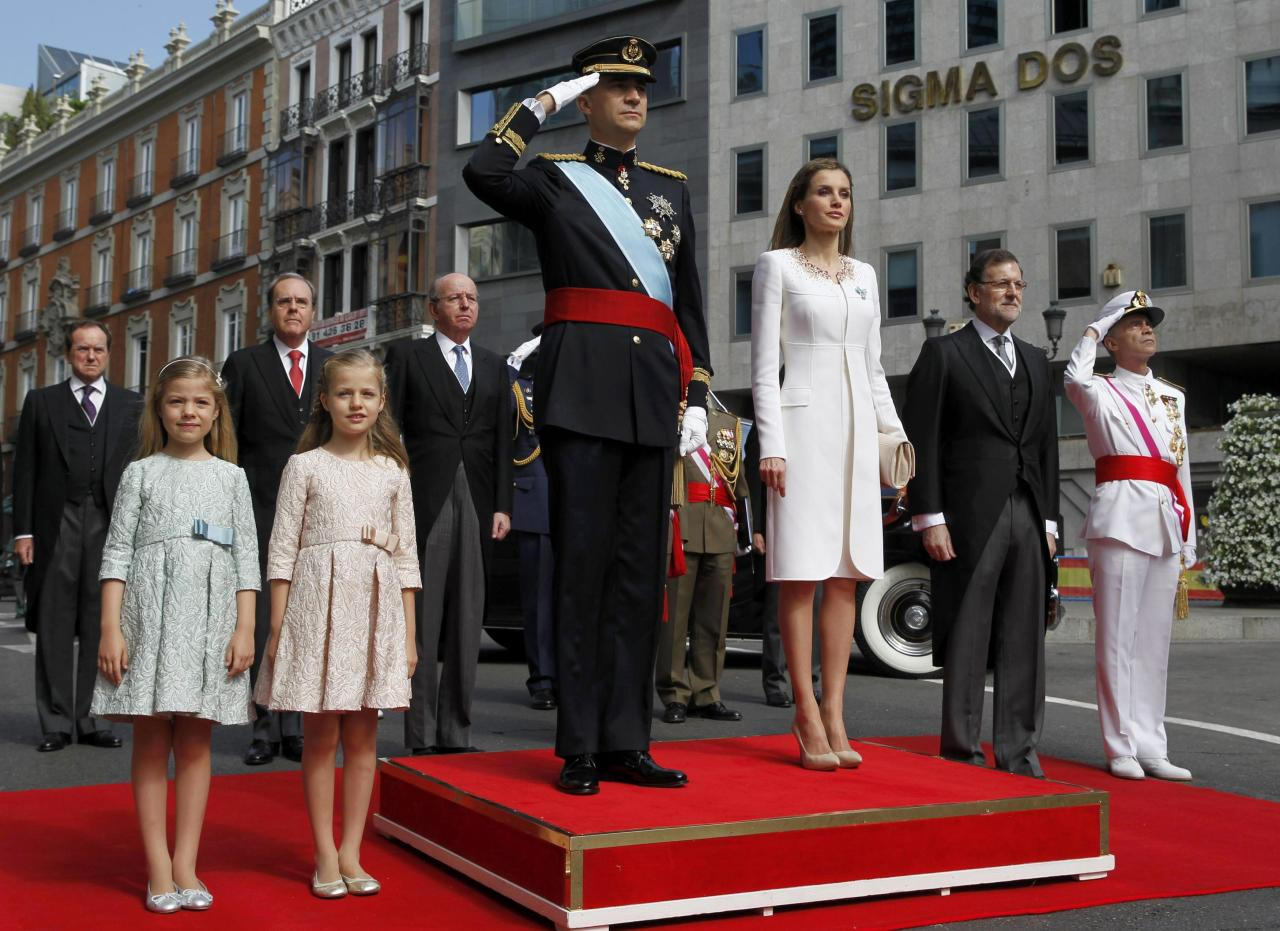 Spain's new King Felipe VI (C), his wife Queen Letizia (3rdR), Princess Leonor (2ndL) and Princess Sofia (L) and Prime Minister Mariano Rajoy (2ndR) review troops as they arrive at the Congress of Deputies to attend the swearing-in ceremony in Madrid, June 19, 2014. Spain's new king, Felipe VI, was sworn in on Thursday in a low-key ceremony which monarchists hope will usher in a new era of popularity for the troubled royal household. REUTERS/Sergio Barrenechea/Pool (SPAIN - Tags: ROYALS POLITICS ENTERTAINMENT)