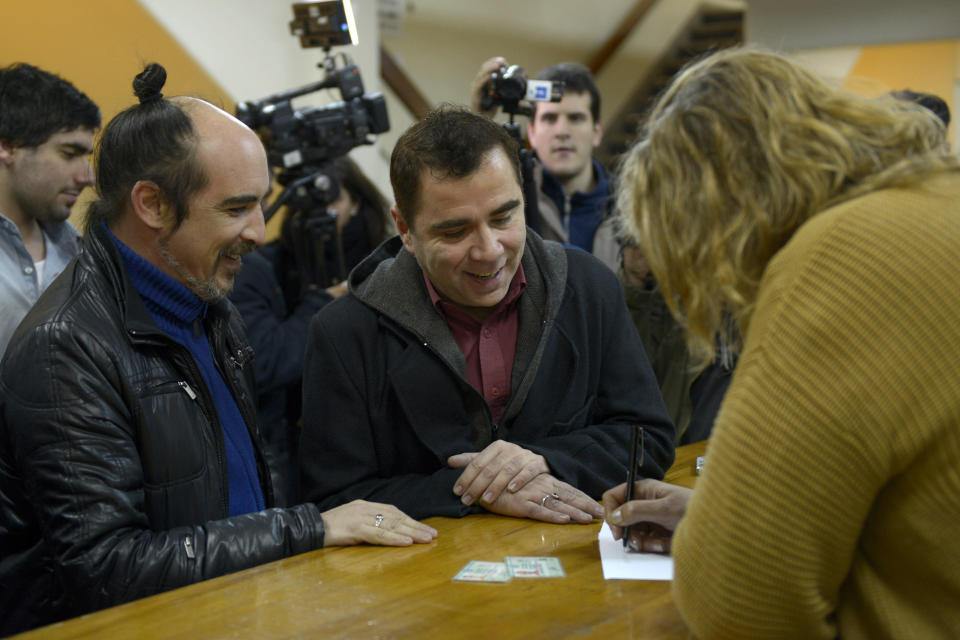 Rodrigo Borda, left, and his partner Sergio Miranda watch a Civil Registry worker take down their information to apply to get married in Montevideo, Uruguay, Monday, Aug. 5, 2013. (AP Photo/Matilde Campodonico)